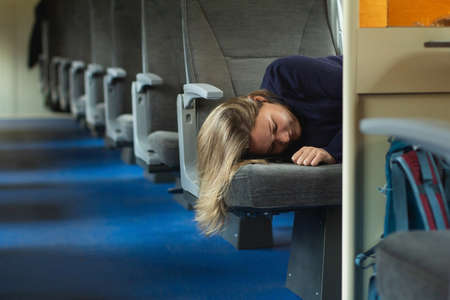 Young woman traveler sleeping inside of suburban train. Empty train seats on the background