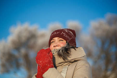 Happy young woman in red winter hat and red mittens on the snow sunny day against blue sky Archivio Fotografico
