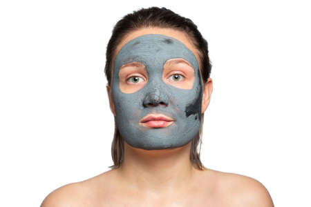 Caucasian woman with a clay or a mud mask on her face over white background. Solving acne problems, cleansing, smoothing, rejuvenating the skin. The texture of a drying clay mask