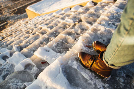 Danger of slipping. Female boots on rough slipper ice surface. A woman in brown leather shoes descends the slippery ice ladder Archivio Fotografico