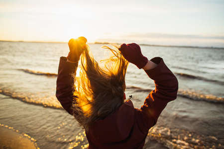 Young woman in the jacket playing with her hair by the winter sea in sunset