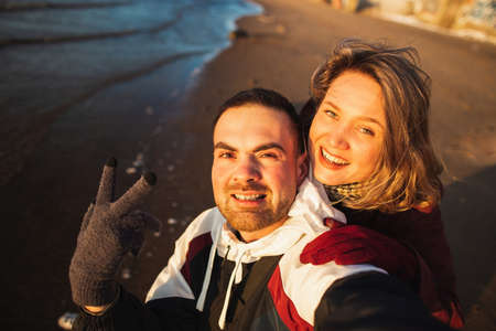 Couple selfing in a smart phone on holidays with the winter beach in the background