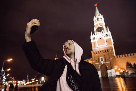 Handsome man in a windbreaker taking selfie overnight against Spassky Tower in Red Square, Moscow