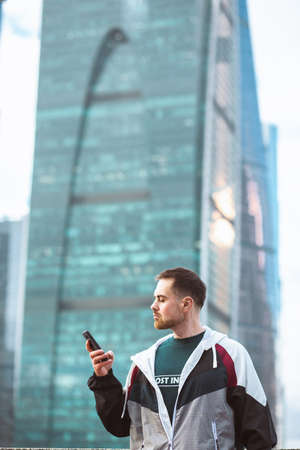 Handsome casual man in windbreaker standing with smatphone on a skyscraper view