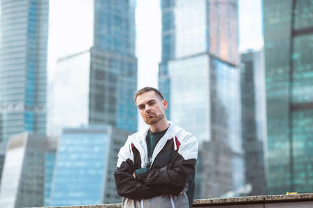 Handsome casual man in windbreaker standing on a skyscraper view