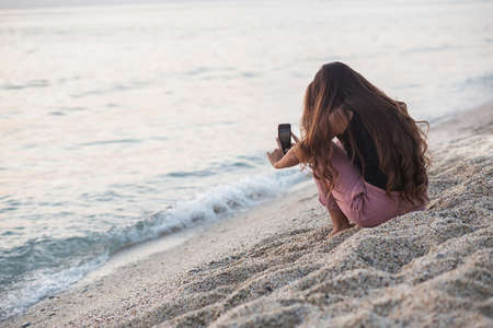 A young girl takes pictures of a sunset on the beach