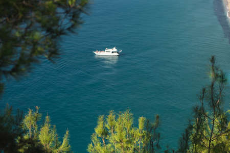 View of the white yacht and turquoise sea and beach from above. Resort vacation concept