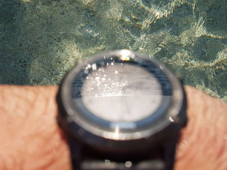 Brutal metal smartwatch on a mans hand with reflection of solar patches of light on water on sapphire glass. Bathing in water-proof watches