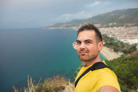 A young Latin man shows a view of the sea bay with turquoise water. Alanya, Turkey