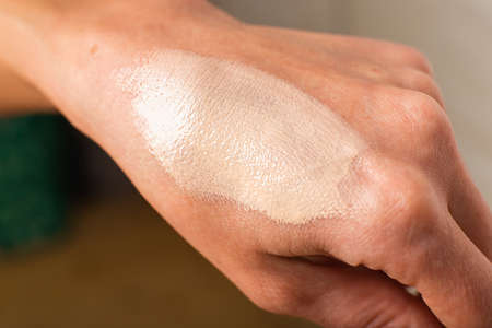 Swatch of tonal foundations on the woman hand closeup texture