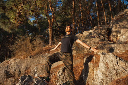 Beautiful man does breathing exercises at sunset in mountain pine forest
