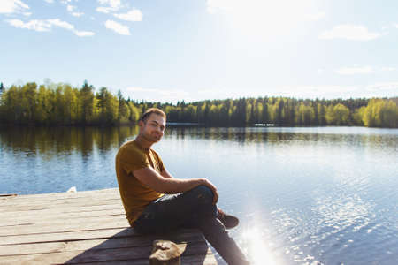 Young handsome man sitting near forest lake, relaxing and meditating in spring or summer sunny day