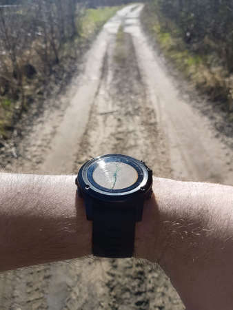 Smart watch show the direction of the route on the forest road 免版税图像