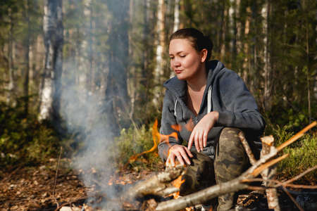 Girl lights a fire for cooking in the spring forest 免版税图像