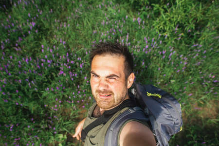Man backpacker in the background of a meadow with purple wildflowers