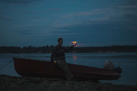 A man in a sweater takes a selfie in the background of a boat by the river on a mystical lunar night 免版税图像