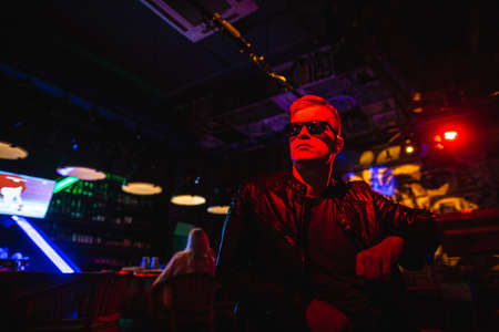 Handsome man in leather jacket with sunglasses and neon lights