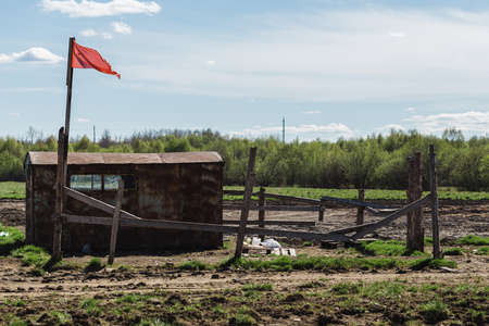 Guards booth with red flag and fields of beds in spring