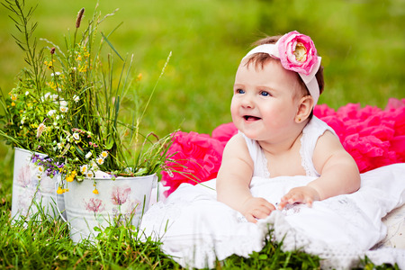 cute newborn girl smiling on grass in pink skirt with flower  photo