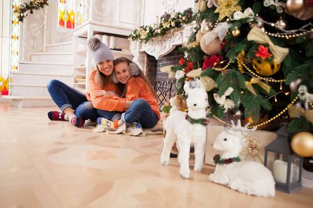 mother and daughter cheerfully cheer near Christmas tree