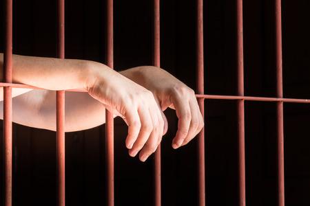 in jail: Cerca mano del colgante musulmanes masculina en la barra en la cárcel.