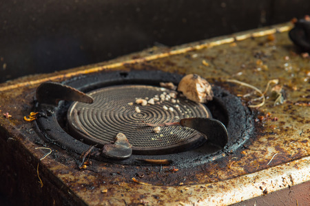 Close up of old broken dirty gas stove in kitchen. Stock Photo