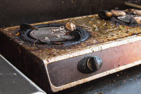 old gas stove: Close up switch of old broken dirty gas stove in kitchen. Stock Photo