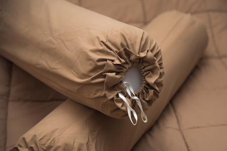 bolster: Close up of brown bolster on the brown blanket. Stock Photo