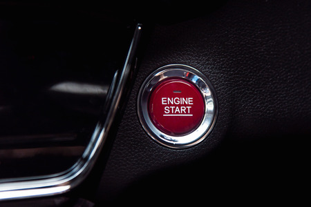 Close up of red start engine button on black car console. Stock Photo