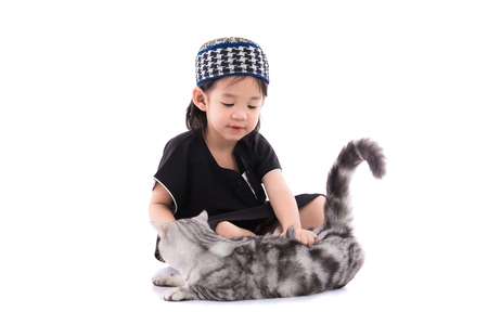 namaz: Close up of cute muslim boy playing with persian cat on white background isolated. Stock Photo