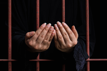 woman prison: Close up hand of muslim woman praying hang on iron bar in jal. Stock Photo