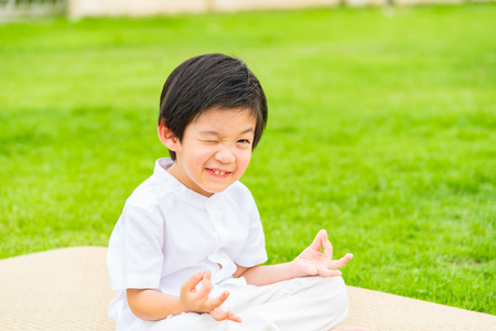 buddhist meditation: Close up of cute buddhist asian boy sit on wooden mat praying and meditation in the garden. Stock Photo