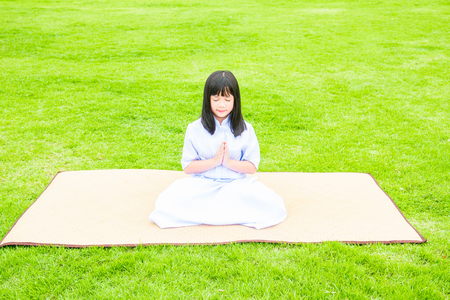 sit up: Close up of beautiful buddhist asian girl sit on wooden mat praying and meditation in the garden.