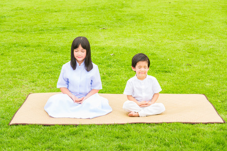 Close up of beautiful buddhist asian children sit on wooden mat praying and meditation in the garden. Imagens