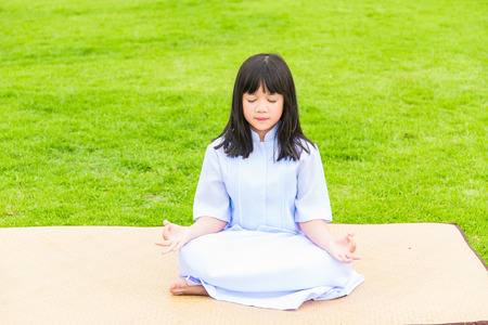 buddhist meditation: Close up of beautiful buddhist asian girl sit on wooden mat praying and meditation in the garden.