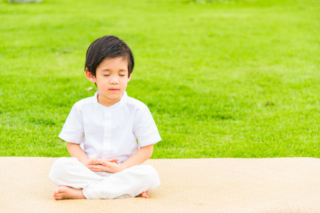 Close up of cute buddhist asian boy sit on wooden mat praying and meditation in the garden. Stock Photo