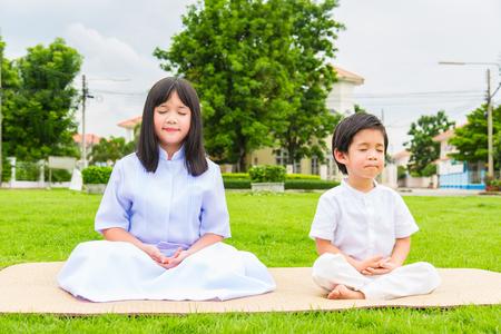 soustředění: Zblízka krásných buddhistických asijských dětí sedí na dřevěné podložce modlí a meditaci v zahradě.