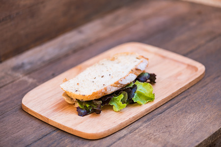 multi grain sandwich: Close up of fresh organic sandwich bread fill with fresh vegetable on wooden dish.