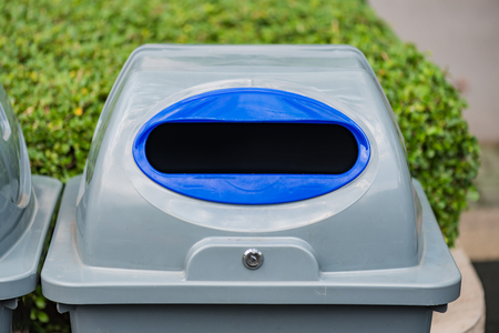 Close up of gray color plastic recycle bin stand in the garden.