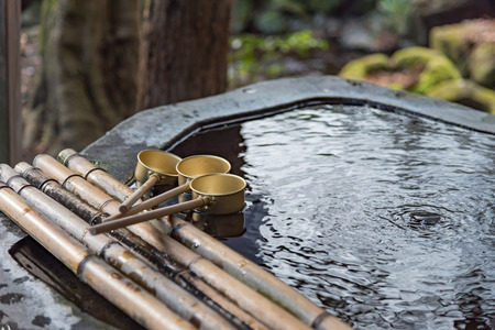 bamboo stick: Close up of brass ladle with bamboo stick for cleaning before praying in japanese shrine yufuin fukuoka japan. Stock Photo
