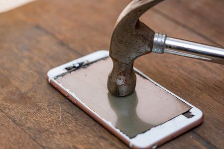 Nahaufnahme von Crash-Handy Smash von rostigen Eisen Hammer auf Holztisch. Standard-Bild