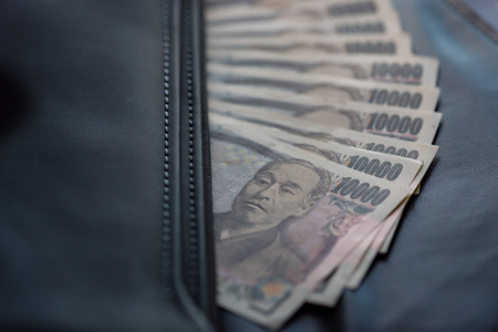 yen note: Close up of ten thounsand yen banknote call ichiman  banknote in japan inside black business leather bag for traveler.