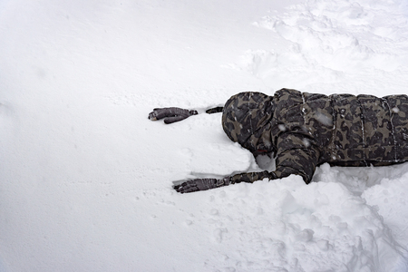 Close up of poor senseless traveler lost his way in the snow forest on the mountain.