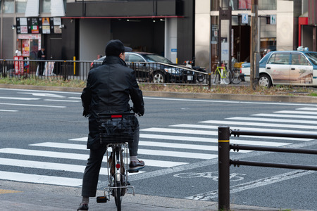 Close up of Japanese people ride bicycle waiting for the sign on the road in Japan.