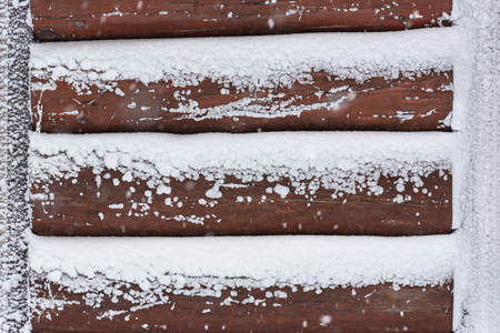 Close up of wooden wall cover by snow in winter.