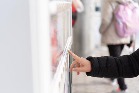 Aziatische vrouwenreiziger die product van automaat in de winter Japan kiest.