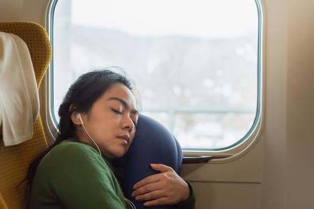 Schöne asiatische Frau bereitet sich auf Reisen vor, indem sie sich ausruht und im Zug schläft.