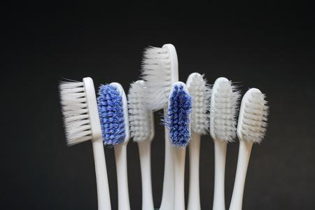 dientes sucios: Desgastado cepillo de dientes en fondo oscuro
