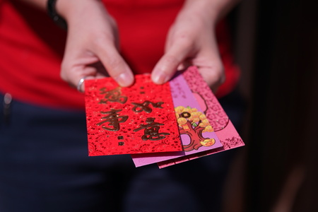felicitation: Red Envelope with blessing words for Chinese New Year Gifts held in hand, Traditional Celebration, China, Happy Chinese New Year