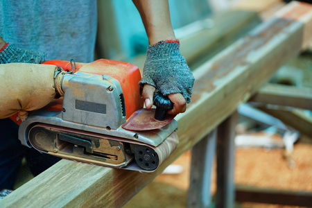 electric material: Man working on the electric wood sanding machine Stock Photo